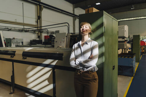 Businesswoman with closed eyes leaning against a cabinet in a factory - KNSF07785