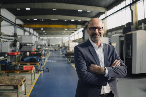Portrait of a smiling businessman in a factory - KNSF07791