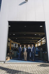Portrait of confident business team standing at factory gate - KNSF07800