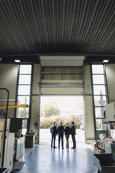 Rear view of business team standing at factory gate - KNSF07803