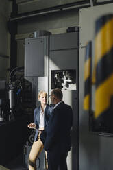 Businessman and businesswoman with tablet talking in a factory - KNSF07806