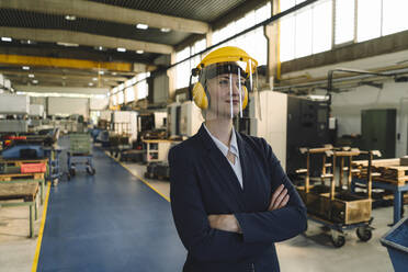 Portrait of a confident businesswoman wearing safety helmet and earmuffs in a factory - KNSF07809