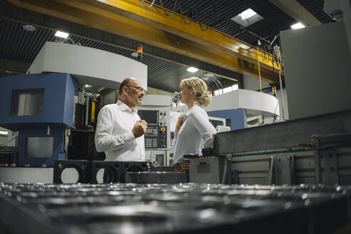 Man and woman talking in a factory - KNSF07815