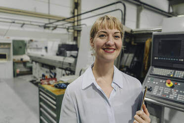 Portrait of a smiling businesswoman with clipboard in a factory - KNSF07824