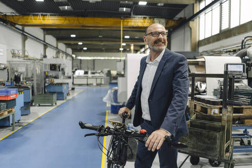Smiling businessman with bicycle in a factory - KNSF07827
