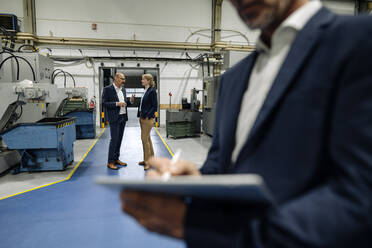 Businessman using tablet in a factory with colleagues talking in background - KNSF07833