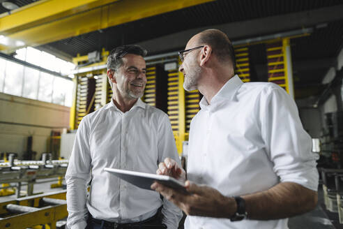 Two businessmen with tablet talking in a factory - KNSF07851