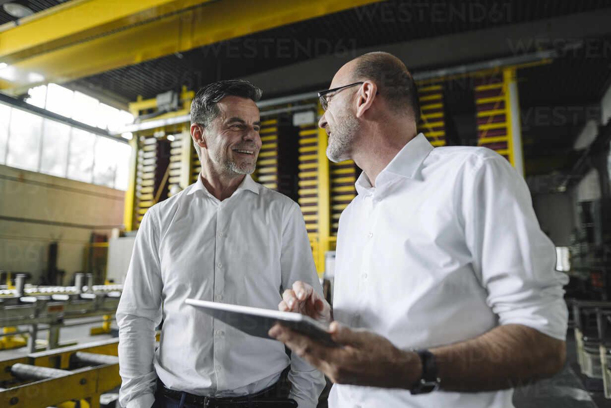 Two businessmen with tablet talking in a factory - KNSF07851 - Kniel Synnatzschke/Westend61