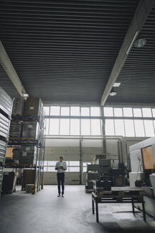 Businessman holding tablet in a factory - KNSF07857