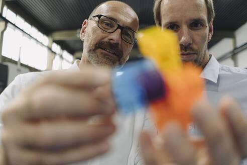 Two men examining workpiece in a factory - KNSF07860