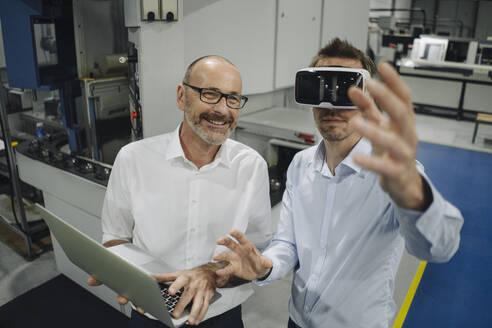 Two men with VR glasses in factory - KNSF07872