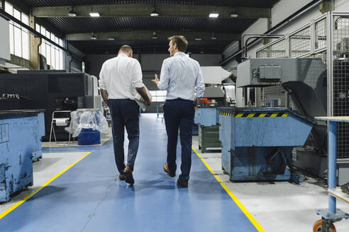Rear view of two men walking and talking in a factory - KNSF07878
