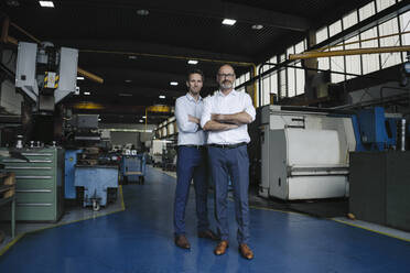 Portrait of two confident men in a factory - KNSF07884