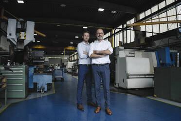 Portrait of two confident men in a factory - KNSF07884