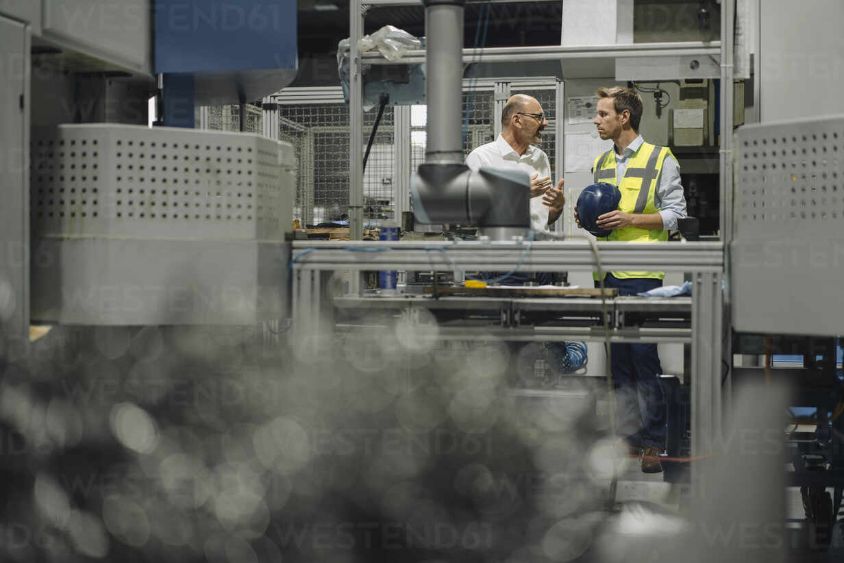 Businessman and man in reflective vest talking in a factory - KNSF07887 - Kniel Synnatzschke/Westend61