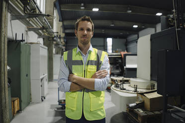 Portrait of a confident man wearing reflectivevest in a factory - KNSF07890