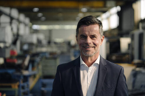 Portrait of a smiling businessman in a factory - KNSF07896
