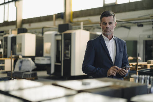 Portrait of a businessman with cell phone in a factory - KNSF07899