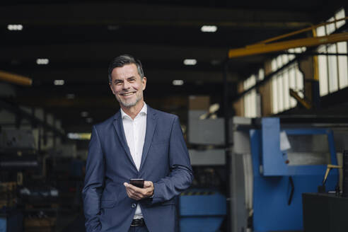 Portrait of a smiling businessman in a factory - KNSF07908