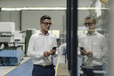 Mature businessman with cell phone in a factory reflected in glass pane - KNSF07911