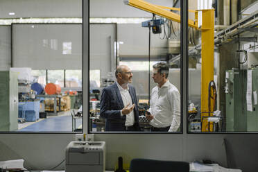 Two businessmen talking in a factory - KNSF07914