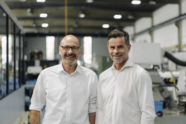 Portrait of two smiling businessmen in a factory - KNSF07917