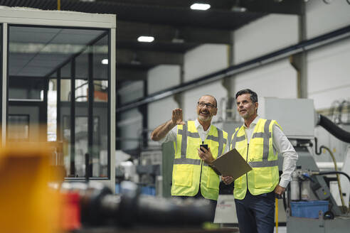 Two men in reflective vests talking in a factory - KNSF07920