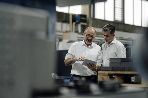 Two businessmen using tablet in a factory - KNSF07923