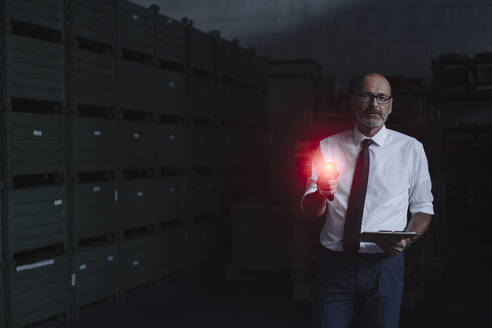 Portrait of man with glowing scanner in factory warehouse - KNSF07932