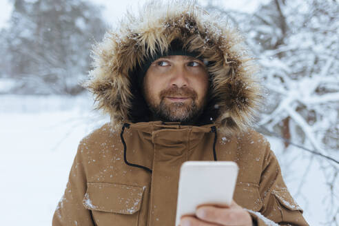 Portrait of pensive man with cell phone in winter - KNTF04423