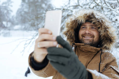 Portrait of smiling man taking selfie with with cell phone in winter - KNTF04426