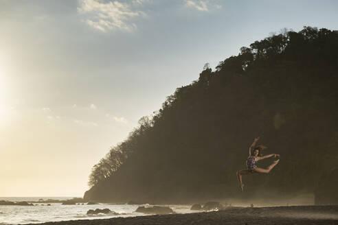 Teenage girl practicing gymnastic on the beach by sunset, Jaco Beach, Costa Rica - AMUF00015