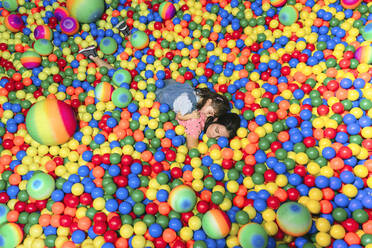 Woman lying with her little daughter among many colourful balls - GEMF03473