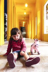 Portrait of little girl sitting on floor with toy unicorn - GEMF03476