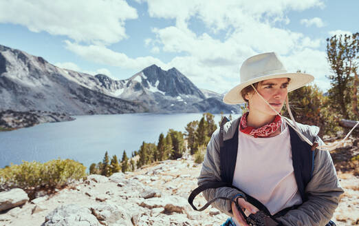 Middle Aged Female in Hat Holding Camera by Lake in Mountains - CAVF76118
