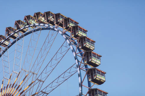 Germany, Bavaria, Munich, Low angle view of Ferris wheelstanding against clear sky - MMAF01290