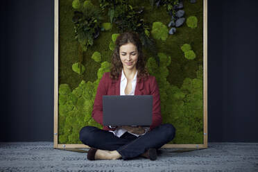Smiling businesswoman sitting on the floor in green office using laptop - RBF07085