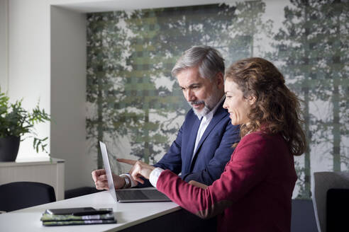 Businessman and businesswoman working together on laptop in office - RBF07094