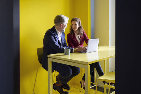 Businessman and businesswoman working together on laptop in office cubicle - RBF07103