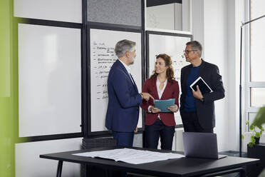 Two businessmen and businesswoman working together on a project in office - RBF07115