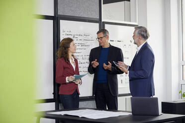 Two businessmen and businesswoman working together on a project in office - RBF07118