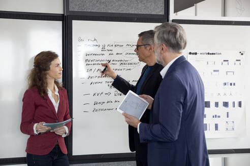 Two businessmen and businesswoman working together on a project in office - RBF07127