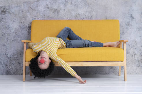 Boy with red clown nose and black hair on yellow couch - HMEF00786