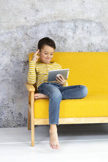 Boy playing with tablet on yellow couch - HMEF00789