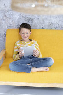 Boy playing with tablet on yellow couch - HMEF00792