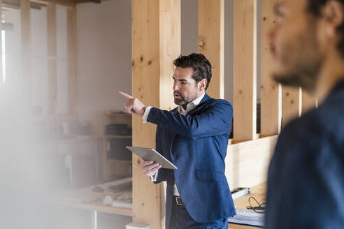 Businessman holding tablet pointing his finger in wooden open-plan office - DIGF09456