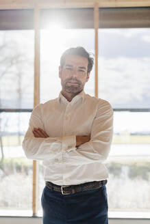 Portrait of confident businessman at the window in open-plan office - DIGF09474