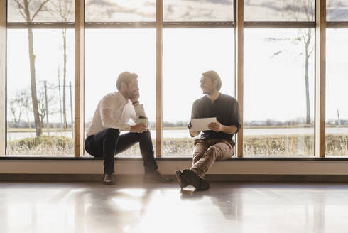 Two businessmen with tablet talking at the window in open-plan office - DIGF09483