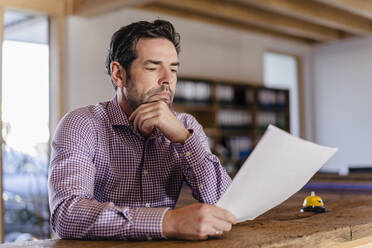 Businessman reading document in wooden open-plan office - DIGF09492