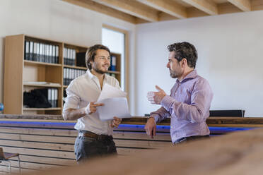 Two businessmen with documents talking in wooden open-plan office - DIGF09501